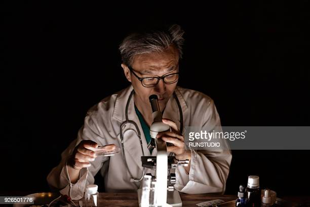 middle-aged doctor examining something through microscope - biochemistry stock pictures, royalty-free photos & images
