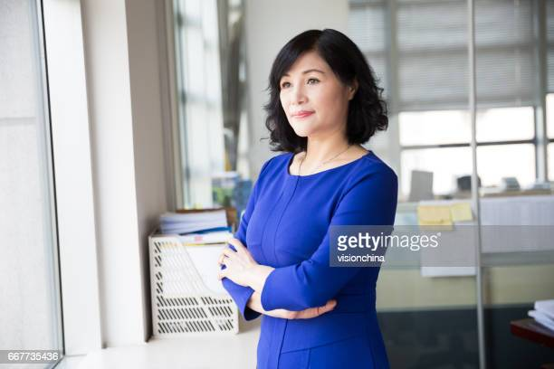 middle-aged female manager posing near by window