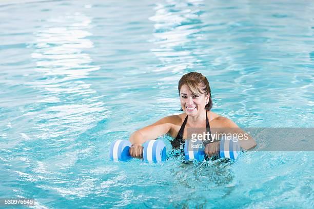 Medio invecchiato donna ispanica facendo acqua aerobica