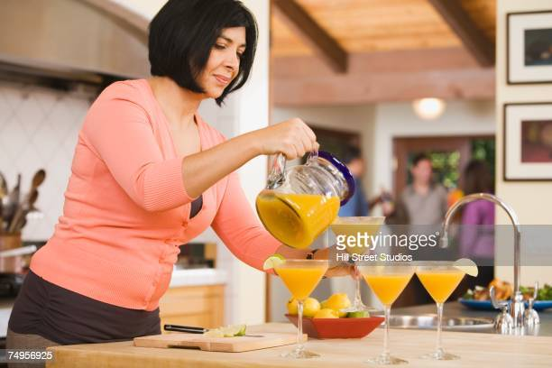 Middle-aged Hispanic woman pouring cocktails