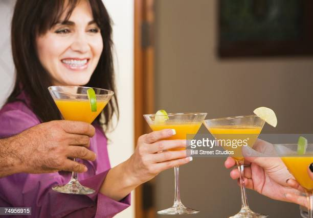 Middle-aged Hispanic woman toasting with friends