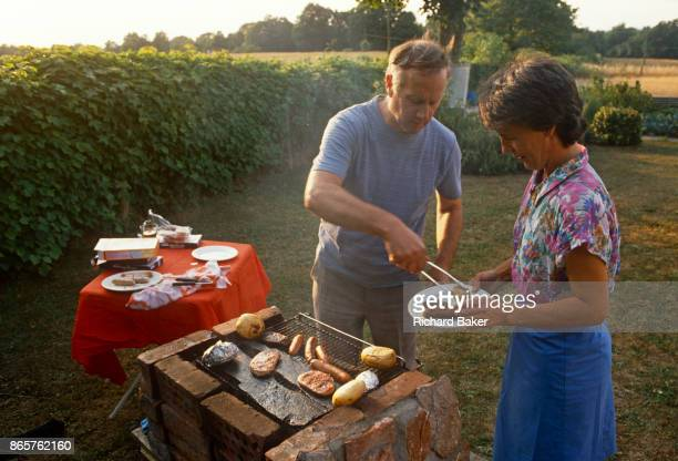 Middle-aged husband serves a plate of meat to his wife from the family home-made BBQ in the back garden on a summer's afternoon, in June 1989, in...