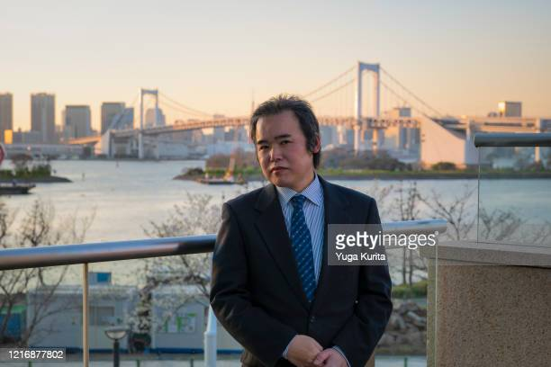 middle-aged japanese businessman standing in front of the tokyo skyline at sunset - front view ストックフォトと画像