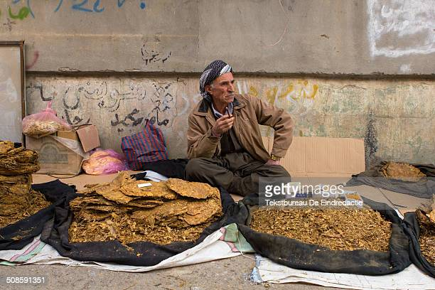 Middle-aged Kurdish-Iraqi street vendor, selling tobacco, wearing traditional baggy trousers and a headscarf, sitting and smoking, on the streets of...