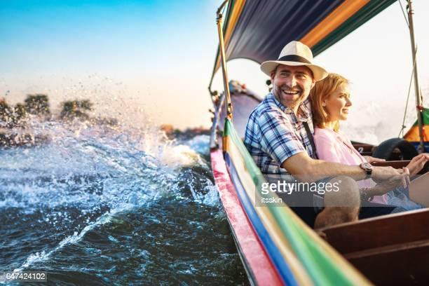 Mann mittleren Alters und seine Begleiter hübsche blonde Lady auf einem Boot fahren in Bangkok