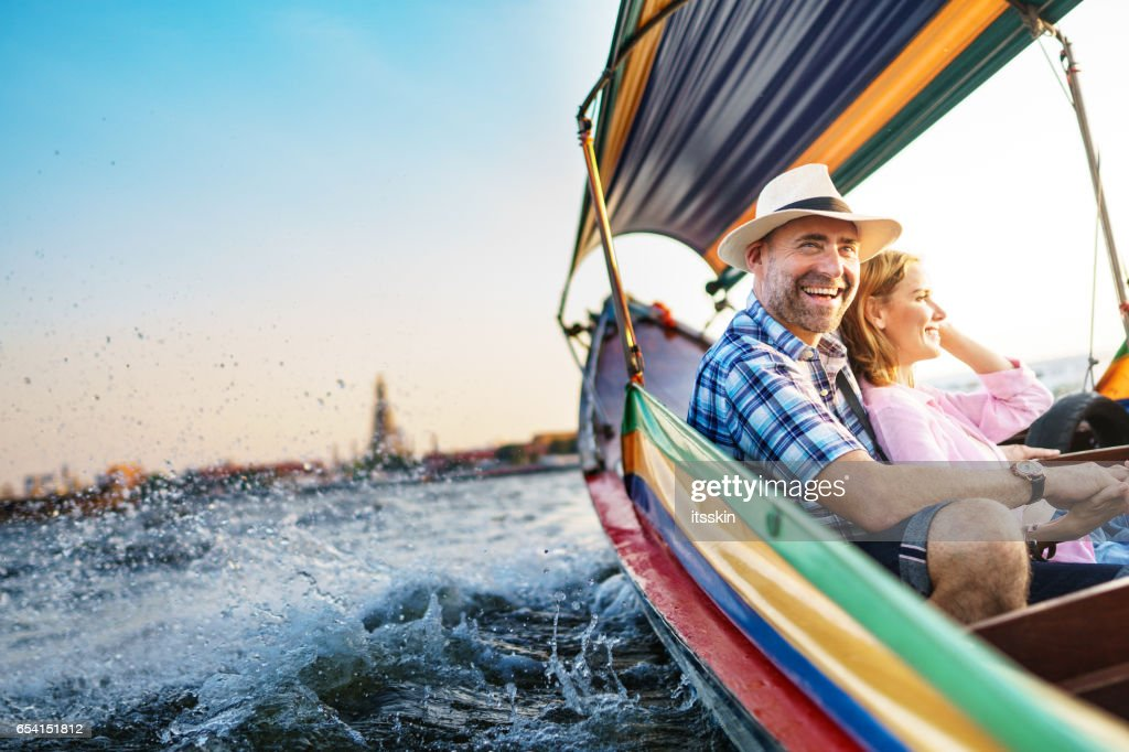 Middle-aged man and his companion handsome blond lady on a boat ride in Bangkok : Stock Photo