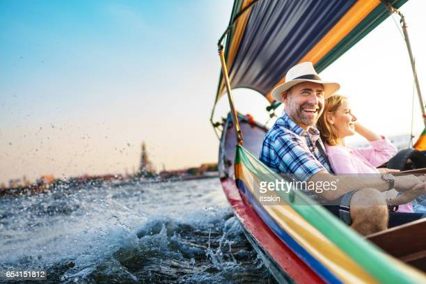 middle-aged man and his companion handsome blond lady on a boat ride in bangkok - watervaartuig stockfoto's en -beelden
