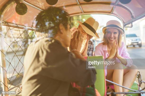 middle-aged man and his companion handsome blond lady on a tuk-tuk ride in bangkok - auto rickshaw stock pictures, royalty-free photos & images