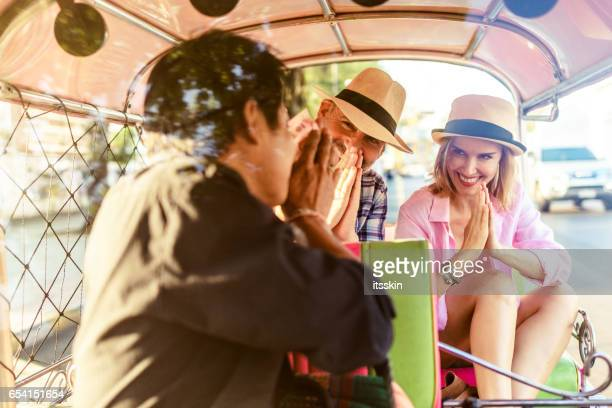 Mann mittleren Alters und seiner schönen blonden Begleitdame auf ein Tuk-Tuk Fahrt in Bangkok