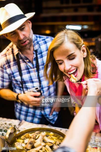 hombre de mediana edad y a su guapo compañero degustación comida callejera de tailandia en bangkok - exotismo fotografías e imágenes de stock