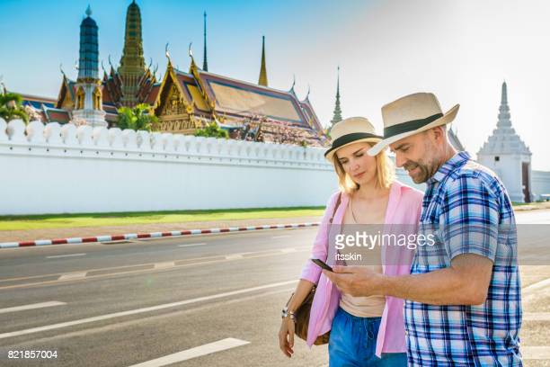 Middle-aged man and his handsome woman on the city walk in Bangkok catching a taxi