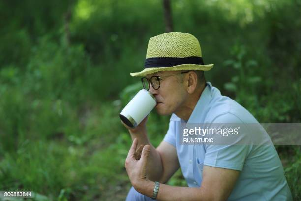 Middle-aged man drinking tea in the park