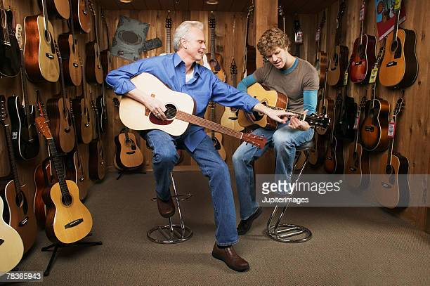 Middle-aged man giving guitar lesson to mid-adult man