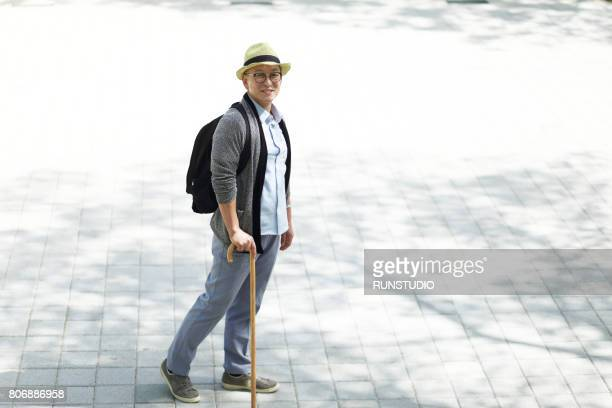 middle-aged man holding a stick - walking cane stock photos and pictures