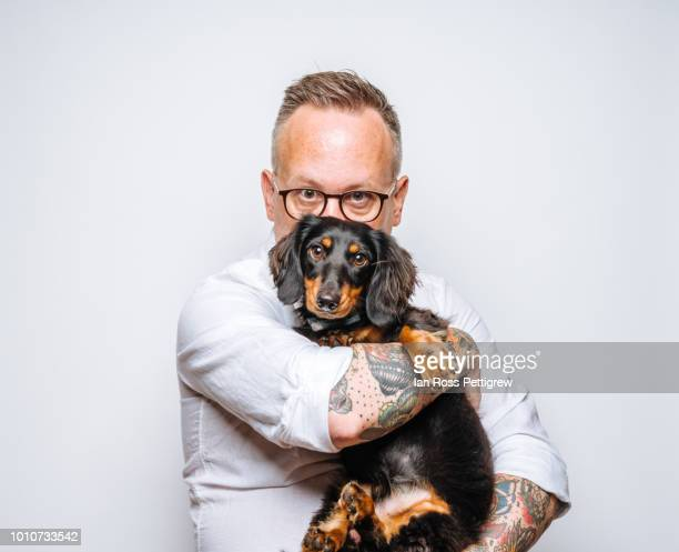 middle-aged man holding dachsund dog - americas next top dog stock pictures, royalty-free photos & images