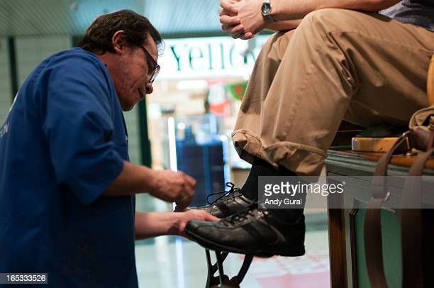 Middle-aged man in a blue coat with rolled sleeves stands before a seated man in order to polish his shoes. The seated man's trouser cuffs are...