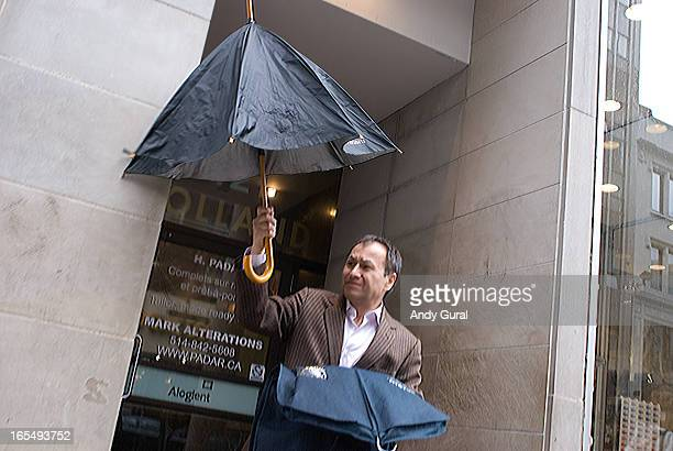 Middle-aged man in a suit jacket with no necktie opens an umbrella. He is holding a suit bag. The shot has motion radial motion blur but the umbrella...