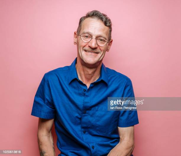 middle-aged man in blue shirt on pink background - sfondo a colori foto e immagini stock