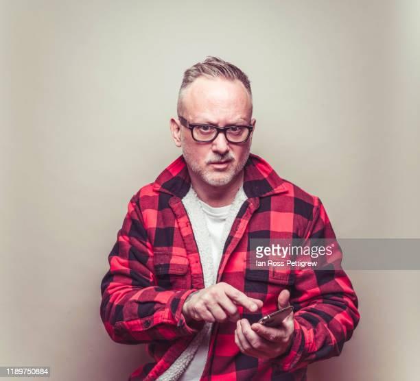 middle-aged man in casual plaid jacket - à carreaux rouges et noirs photos et images de collection