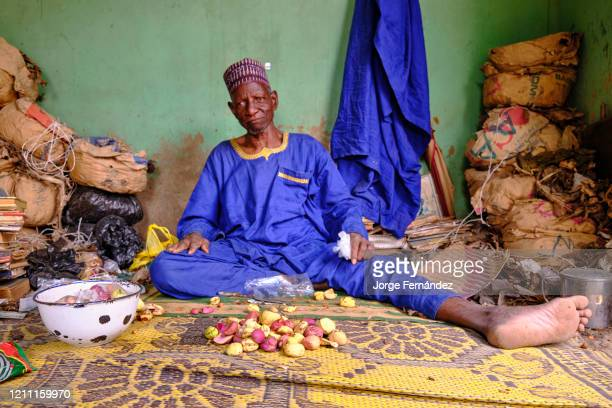 Middleaged man in traditional Hausa clothing selling betel nut at a market stall in Kano