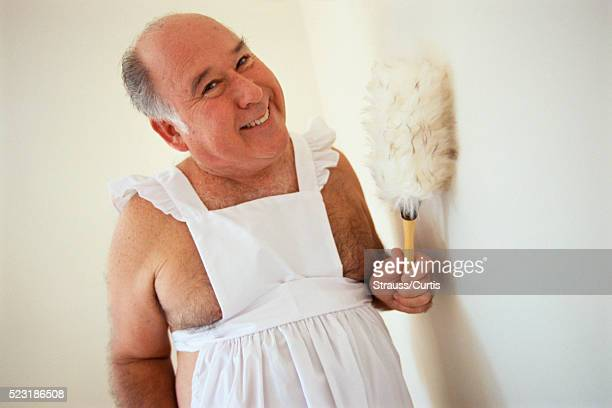 Middle-aged Man in White Apron Dusting