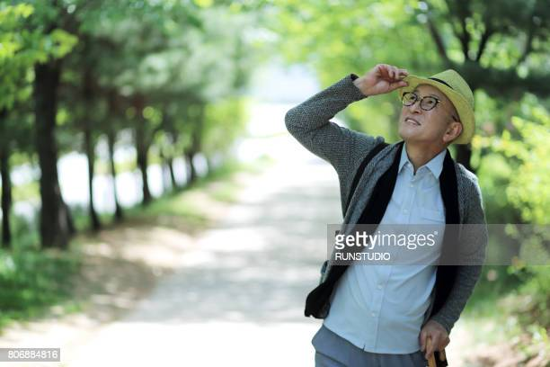 Middle-aged man looking at the sky on a jogging course