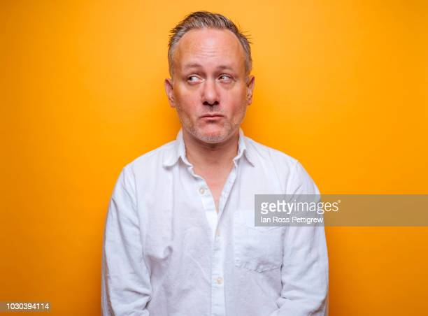 middle-aged man on yellow background - reizen stock-fotos und bilder