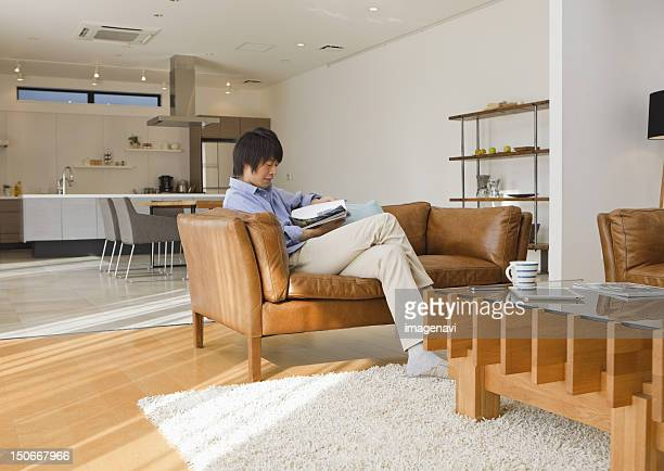 Middle-aged man reading a magazine on a sofa