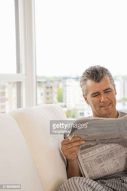 Middle-aged man reading newspaper on sofa