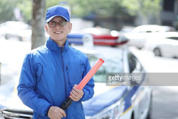 middle-aged man sees a part-time job of traffic guidance - blue hat stock pictures, royalty-free photos & images
