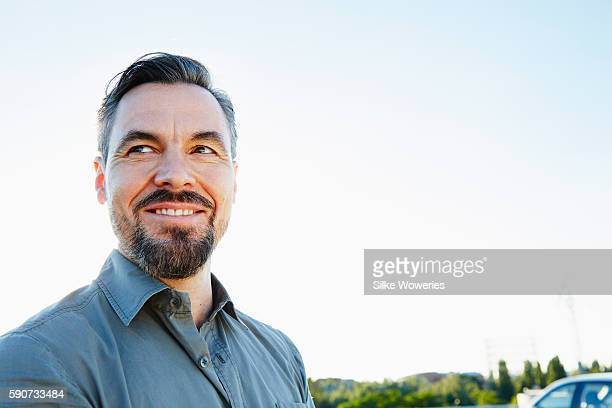 middle-aged man standing beside his car - handsome 50 year old men stock photos and pictures