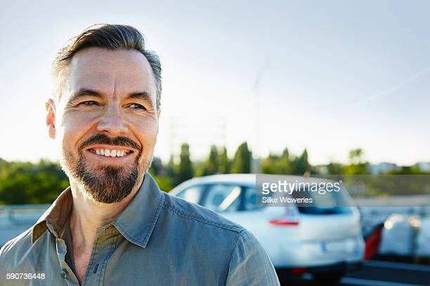 middle-aged man standing beside his car