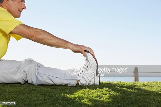 middle-aged man stretching - human body part stock-fotos und bilder