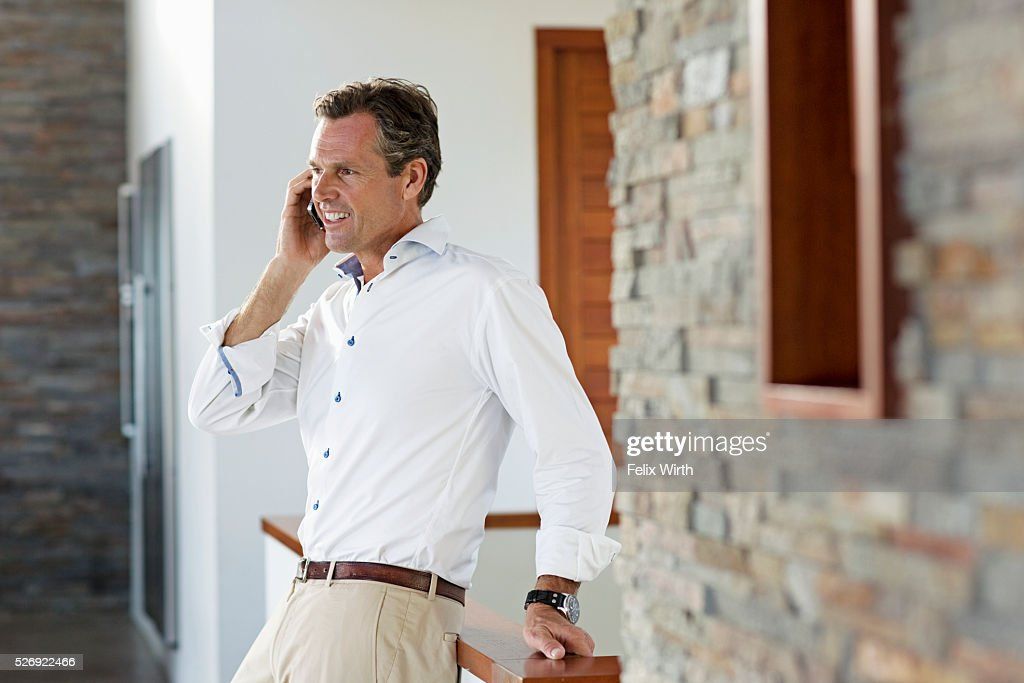 Middle-aged man talking on phone at home : Foto stock