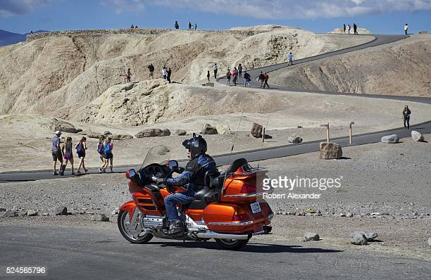 A middleaged man traveling on a Honda touring motorcycle visits Zabriskie Point a popular attraction in Death Valley National Park on March 29 2016...
