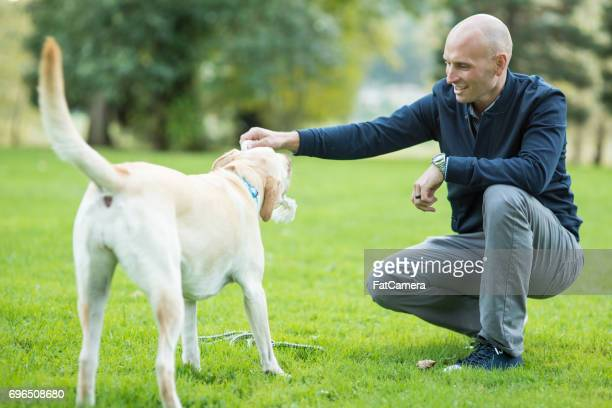 Middle-aged man walking his dog outside in park on sunny day