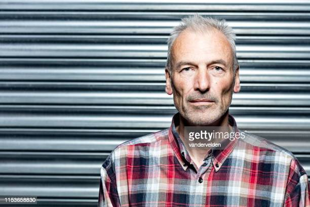 middle-aged man wearing a checked shirt - macho stock pictures, royalty-free photos & images