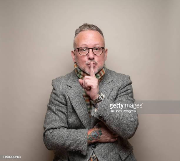 """middle-aged man wearing blazer and scarf gesturing """"quiet"""" - silêncio - fotografias e filmes do acervo"""