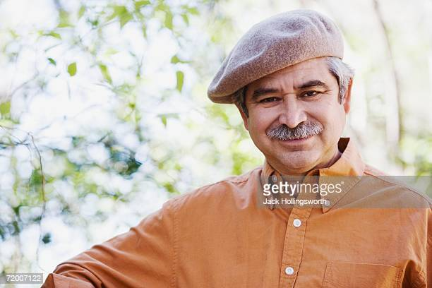 Middle-aged man wearing cap outdoors