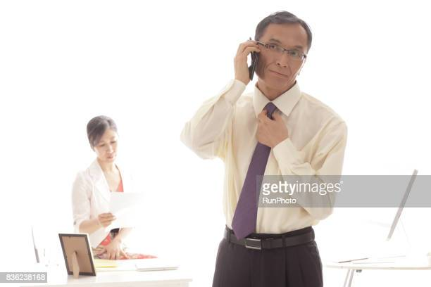 middle-aged man who is grabbing a tie and calling with a smartphone