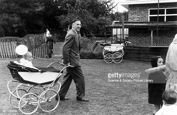 Middleaged man with bad teeth pulling a pram containing a baby and a balloon Photographer Tony RayJones created most of his images of the British at...