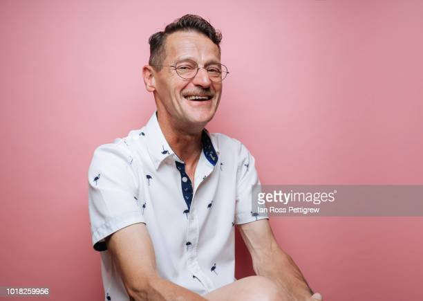 middle-aged man with glasses on pink background - one mature man only stock pictures, royalty-free photos & images