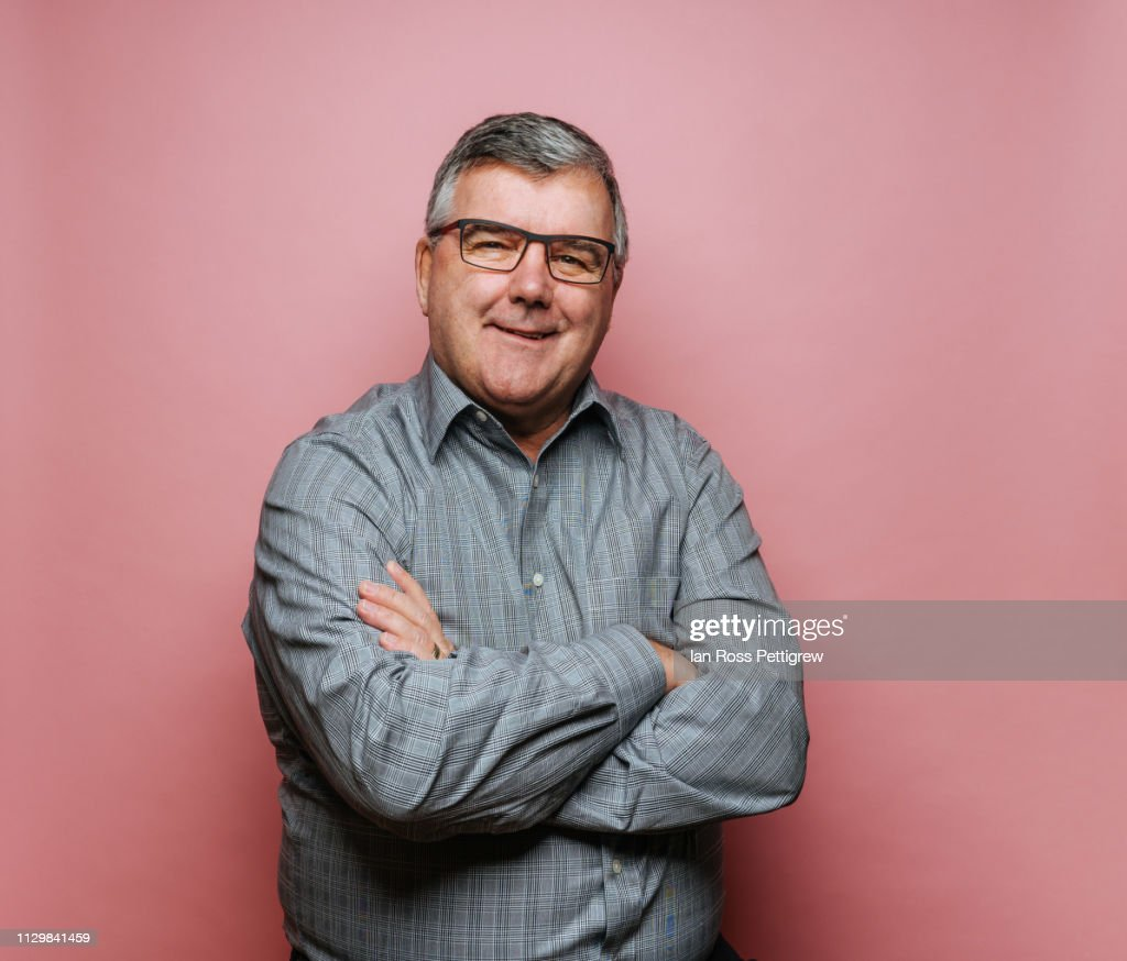 Middle-aged man with glasses on pink background : Foto de stock