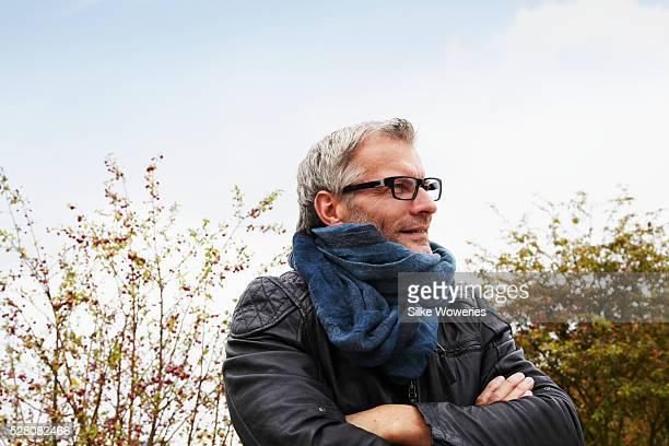 middle-aged man with leather jacket in park - schal stock-fotos und bilder