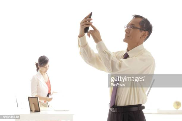 Middle-aged manipulating smartphone