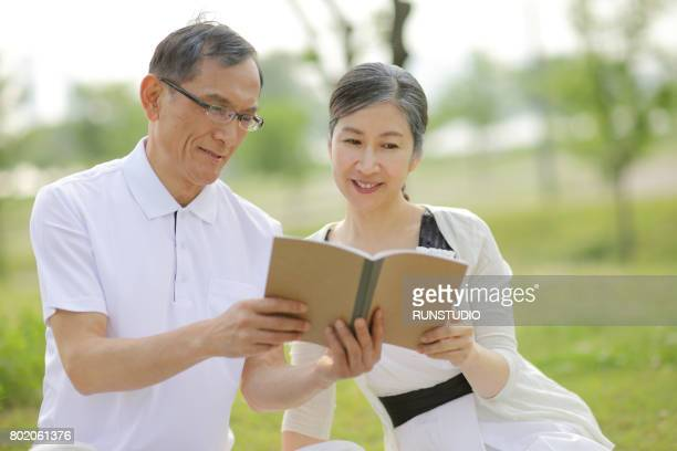 Middle-aged men and women looking at books together