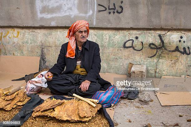 A middleaged street vendor wearing traditional Kurdish clothing including baggy trousers and a red headscarf sitting smoking and selling tobacco on...