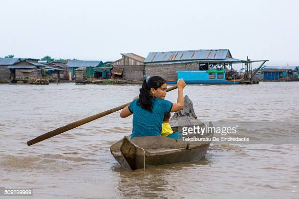 Middle-aged woman and her young child, in a small rowing boat, early in the morning, on the Tonle Sap River, at the floating village of Chong Kos,...
