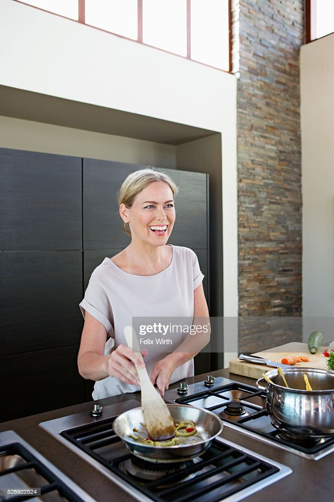 Middle-aged woman cooking dinner : Stock-Foto
