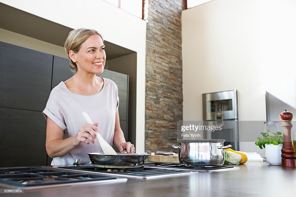 Middle-aged woman cooking dinner : Stockfoto